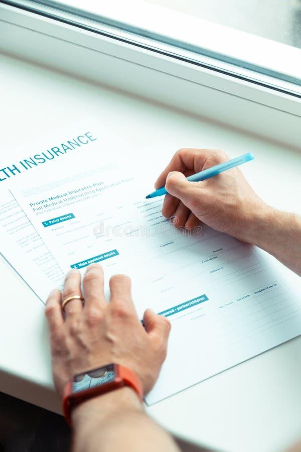 Undertecknande legitimationshandlingar för man, medan köpa privat medicinsk försäkring fotografering för bildbyråer