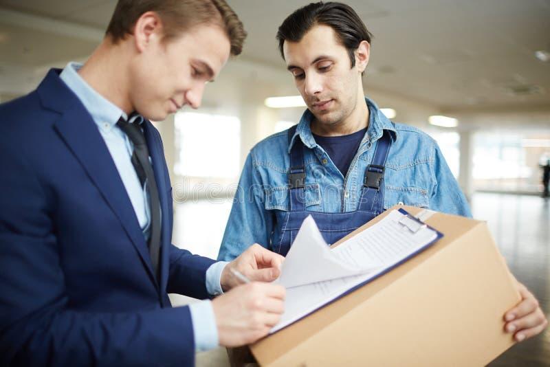 Undertecknande leveranslegitimationshandlingar arkivfoton