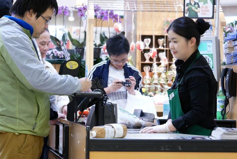 Undertecknande namn för folk för att betala kreditkorten för att köpa foods på kontrollräknaren royaltyfria foton