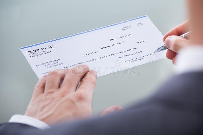 Undertecknande pengarcheck för Businessperson arkivbild
