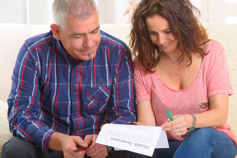 Undertecknande sjukförsäkringavtal för par royaltyfri foto