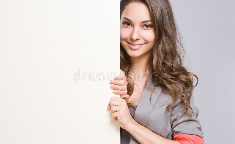 Den eleganta unga affärskvinnan med tom vit undertecknar. arkivbilder
