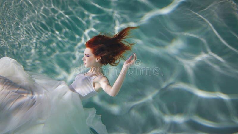 Undervattens- flicka Härlig rödhårig kvinna i en vit klänning som simmar under vatten royaltyfri foto