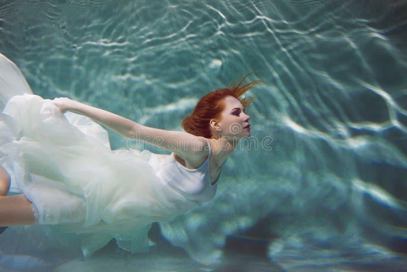 Undervattens- flicka Härlig rödhårig kvinna i en vit klänning som simmar under vatten royaltyfria foton