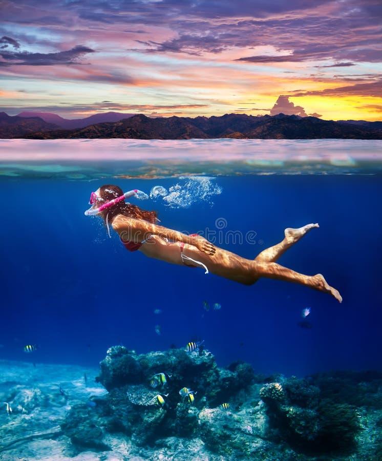 Undervattens- fors av en ung kvinna som snorklar i ett tropiskt hav a royaltyfri bild