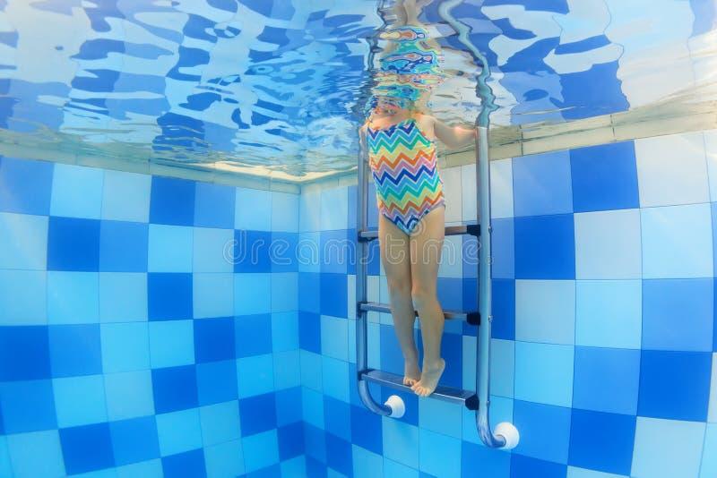 Undervattens- foto av ett barn på simbassängtrappa arkivbilder