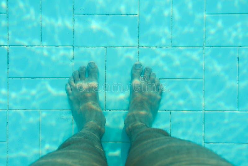Undervattens- foto, botten av simbassängen med blåa tegelplattor, manben som står på det royaltyfri fotografi