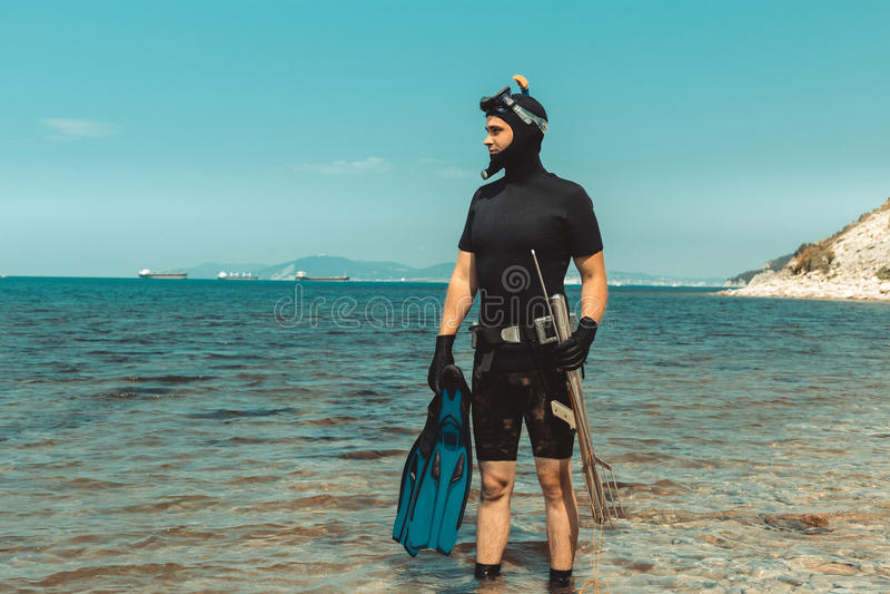 Undervattens- Hunter Man In Diving Suit med utrustning går till havet i sommar utomhus royaltyfri foto