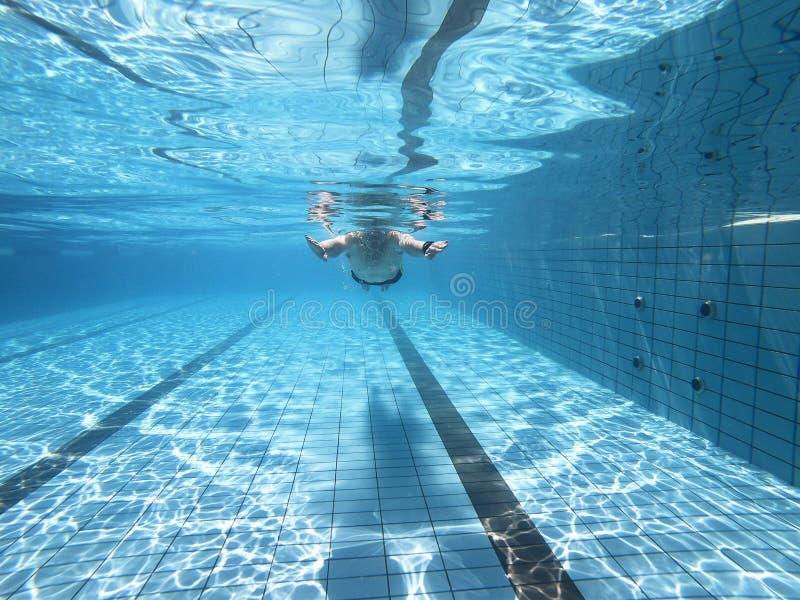 Undervattens- sikt av mannen i simbassäng royaltyfria foton
