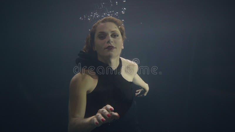 Undervattens- simbassäng för brunettkvinna på mörk bakgrund royaltyfria foton