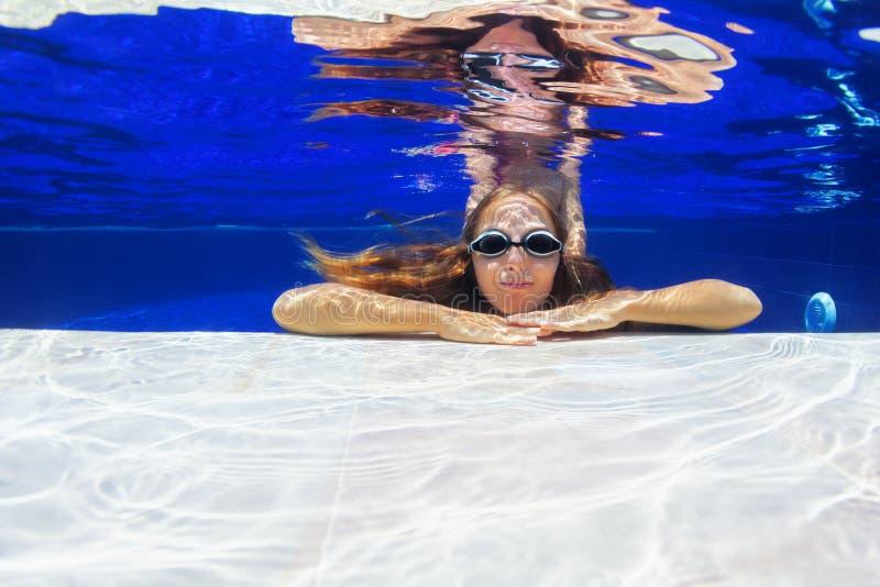 Undervattens- stående av den unga kvinnan i simbassäng royaltyfria bilder