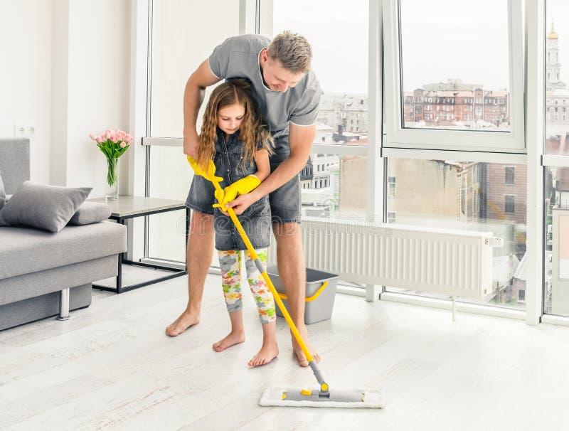Undervisande dotter för fader hur man gör ren med golvmopp royaltyfria bilder