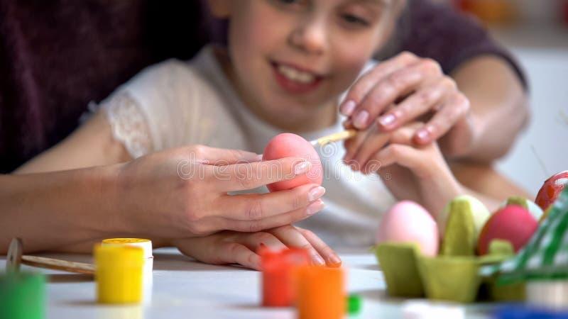 Undervisande dotter för moder som målar påskägg, familjferietraditioner, borste royaltyfria bilder