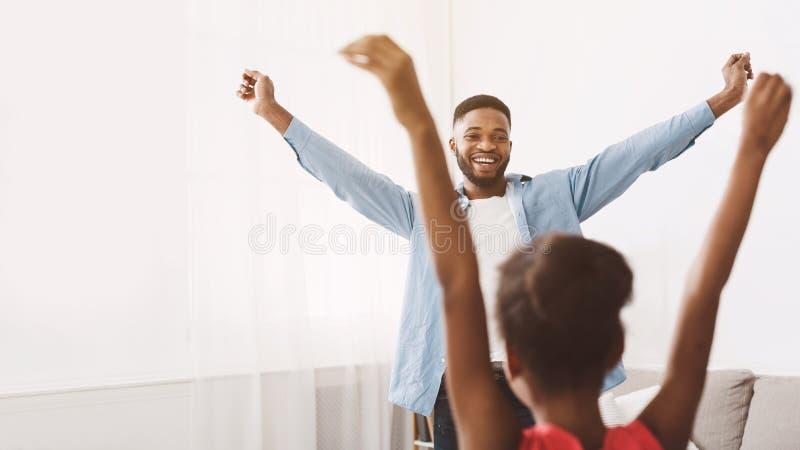 Undervisande fader för liten dotter som hemma dansar royaltyfria foton