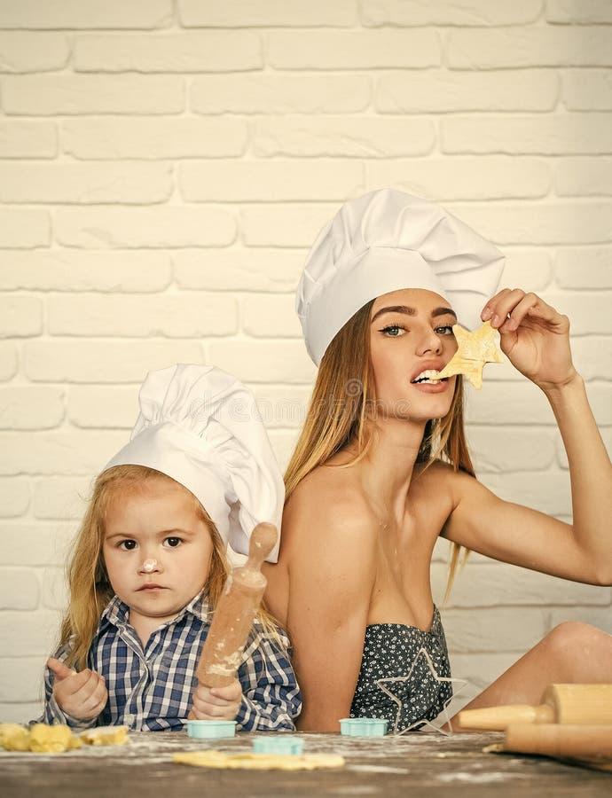 Undervisande kulinariska konster Flicka- och pojkematlagning på den vita tegelstenväggen royaltyfria bilder