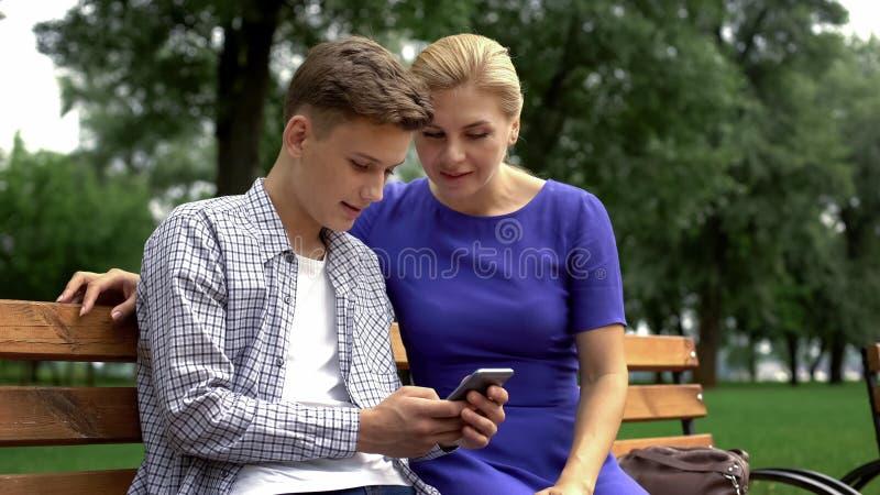 Undervisande moder för son som använder applikationen på smartphonen, nya tekniker, grej royaltyfri fotografi