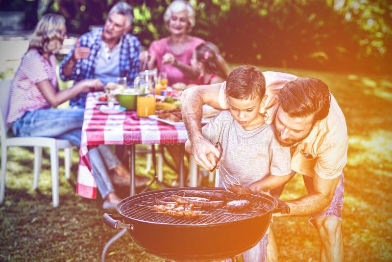 Undervisande son för fader som lagar mat på grillfest med familjen royaltyfri bild