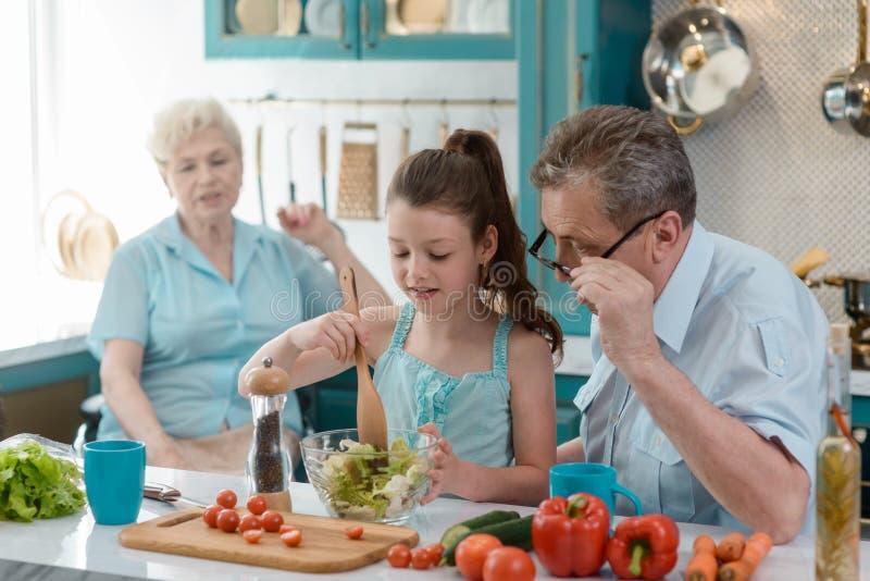 Undervisande sondotter för farfar som ska lagas mat fotografering för bildbyråer