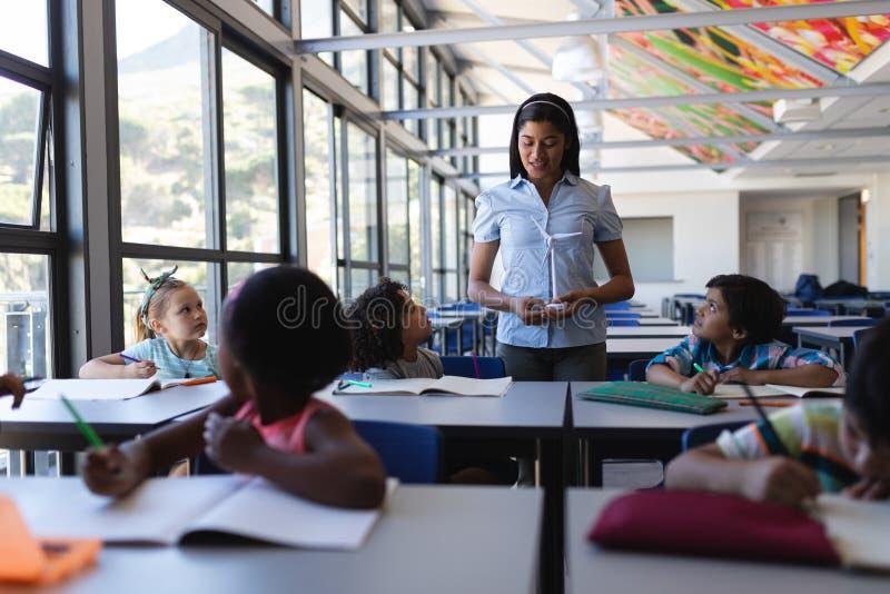 Undervisande student för lärarinna på skrivbordet i klassrum royaltyfri foto