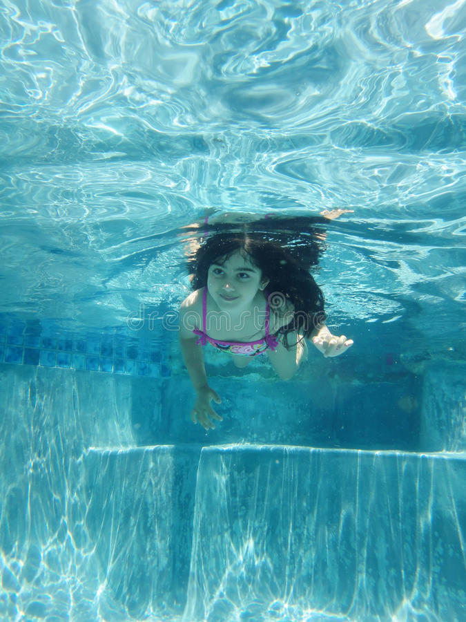 Underwater. Little girl swimming with eyes open stock photography