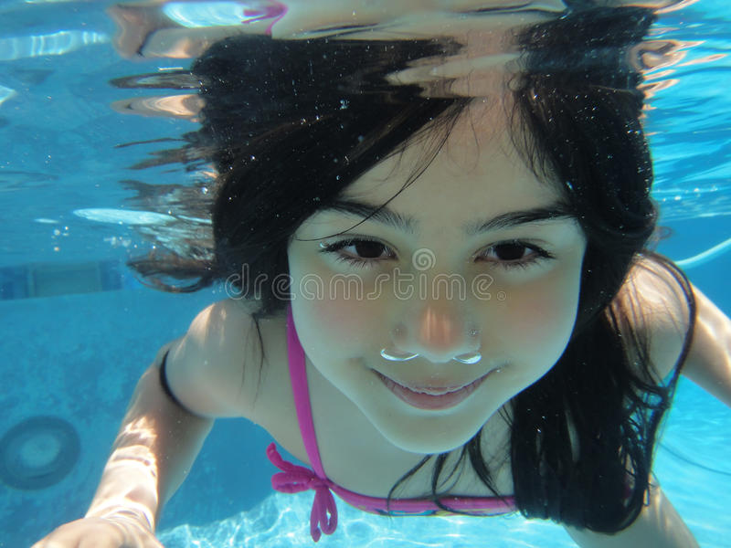 Underwater closeup. Close up of a child swimming deep in the pool royalty free stock images