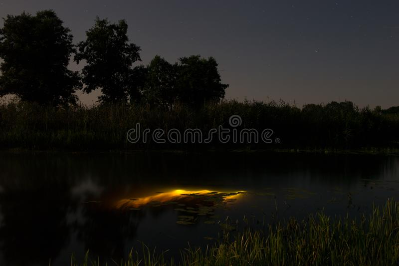 Underwater diving at night with flashlight. Light from river bottom. Full moon over foggy river Stohid. Moon light at night stock photography