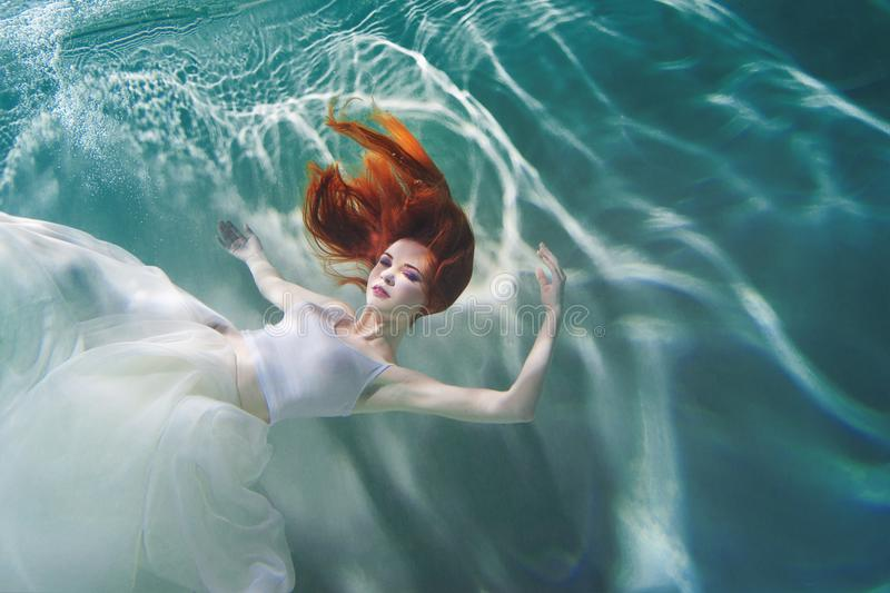Underwater girl. Beautiful red-haired woman in a white dress, swimming under water. stock image