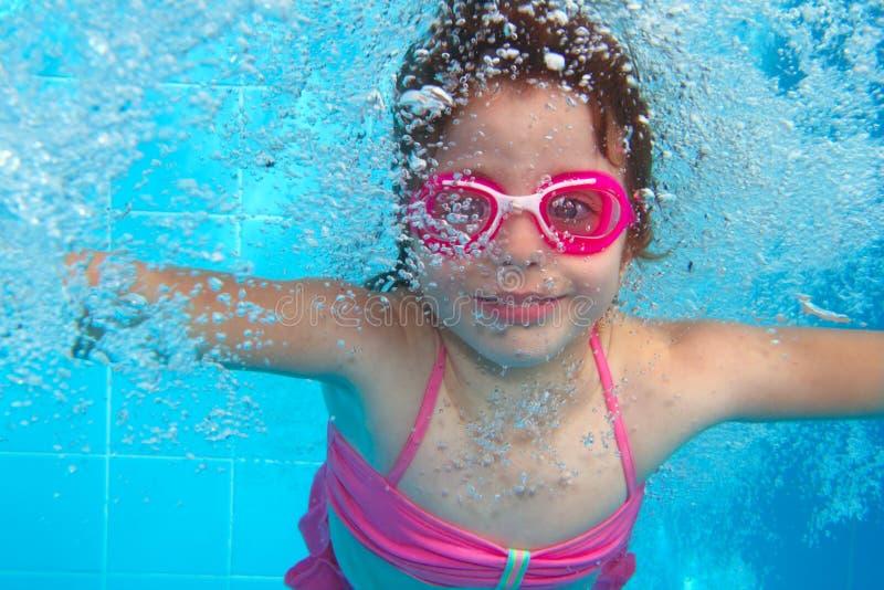 Underwater little girl blue swimming pool stock photos