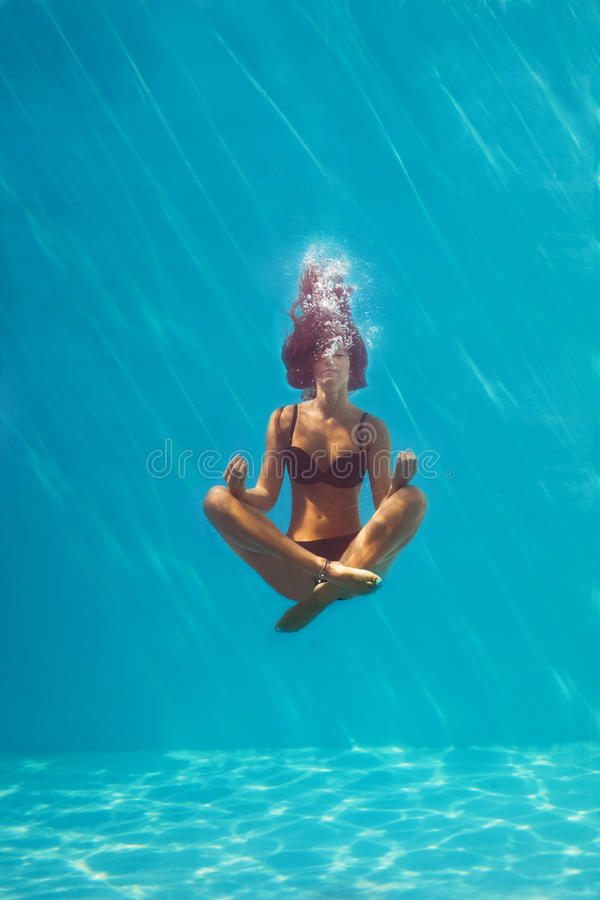 Underwater meditation. Young woman in black bikini in yoga position underwater in diving aquarium, full body shot, front view through the glass stock image