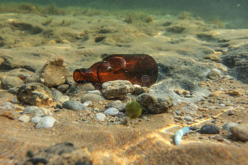 Underwater photo, discarded small beer bottle on sea floor. Ocean littering concept royalty free stock image
