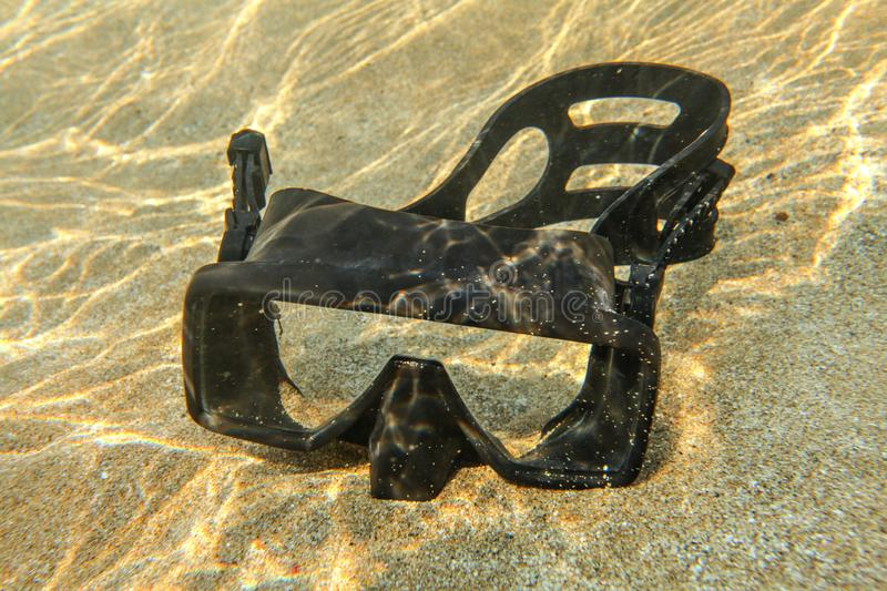 Underwater photo - light from sun refractions at black diving mask sitting in shallow water on clear sand royalty free stock photo