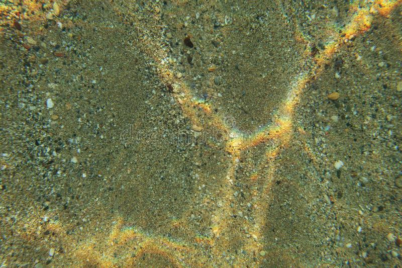 Underwater photo, shallow sea bottom floor seen from top, light refraction making rainbow glares on sand. Abstract marine royalty free stock photography