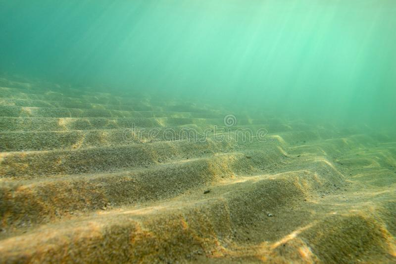 Underwater photo, small sand `dunes ` shot diagonally so in this perspective they form stairs, sun rays coming from sea surface. A royalty free stock images
