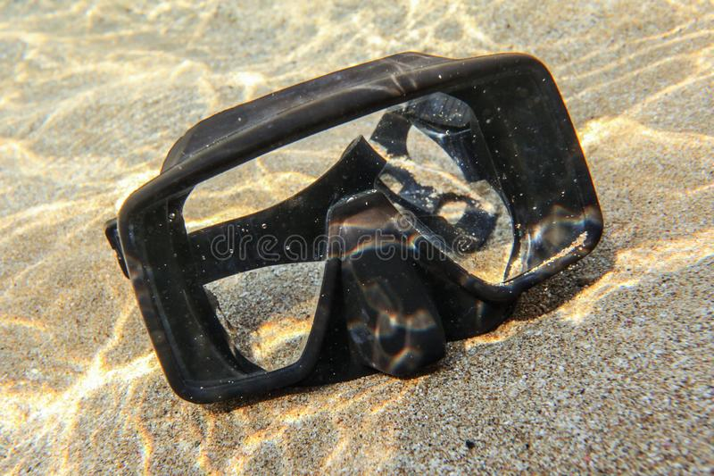 Underwater photo - sun shining to rubber black diving mask on sand in shallow water stock image