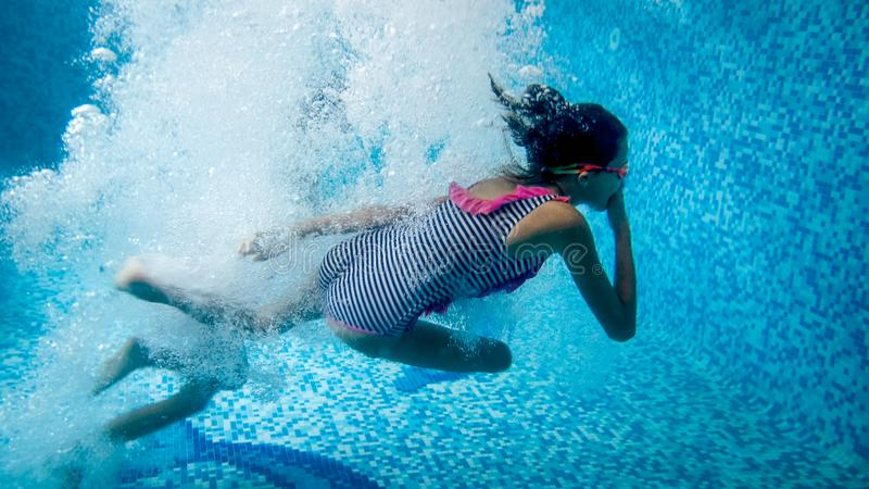 Underwater image of two teenage girls jumping in swimming pool at summer hotel resort royalty free stock photo