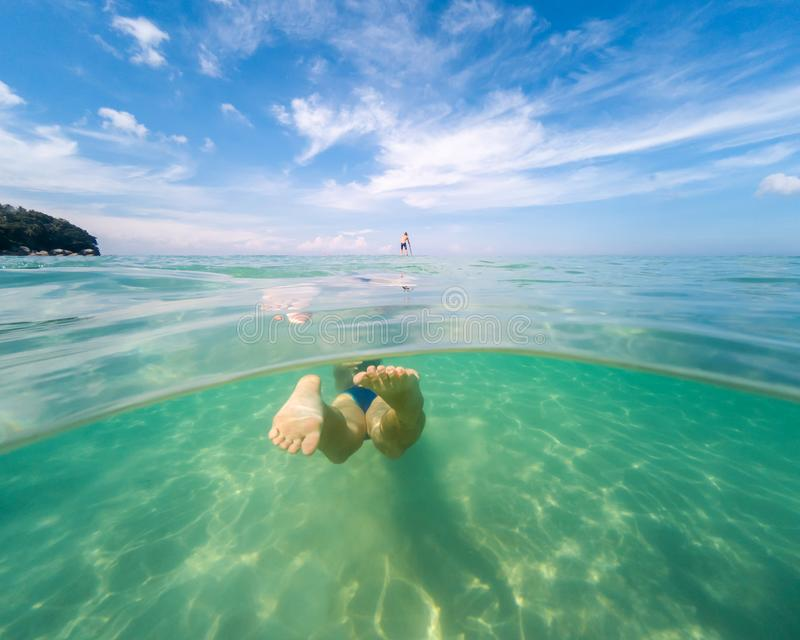 Underwater photo of woman swimming in ocean. View from the back. Split view cross section of sea water and blue sky royalty free stock photography