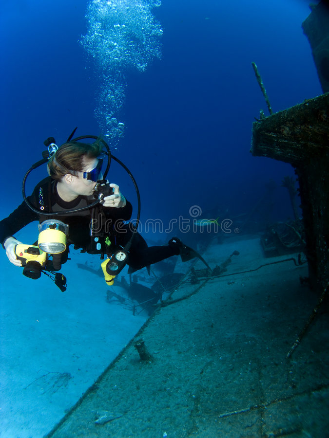 Underwater Photographer looking at a Sunken Ship. With Regulator in her hand stock photography