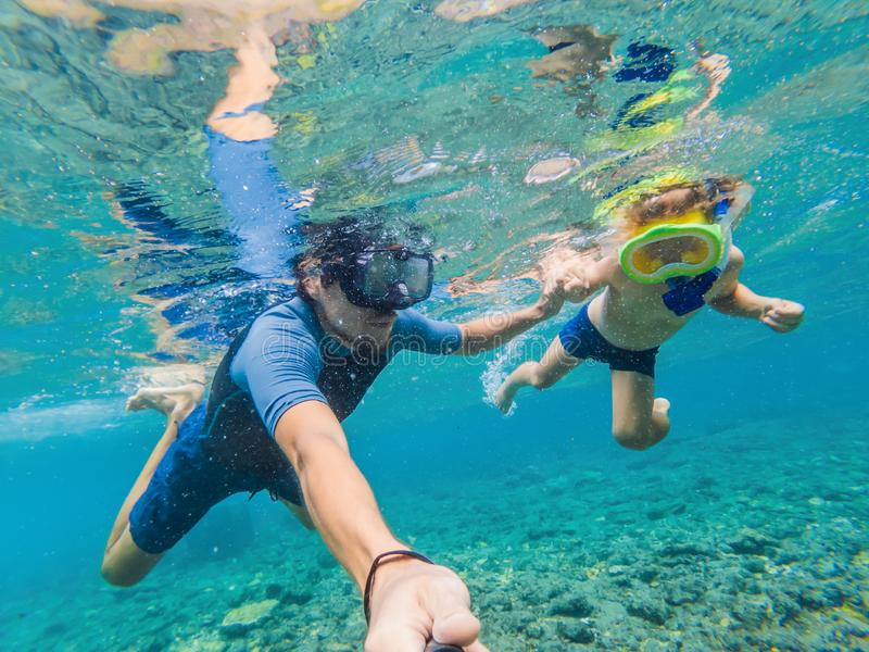 Underwater portrait of father and son snorkeling together stock photo