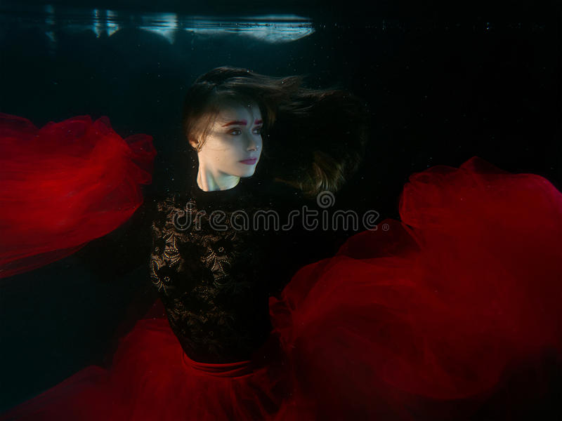 Underwater portrait of young beautiful woman in black dress stock image