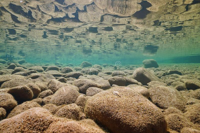 Underwater rocky riverbed reflected in surface royalty free stock photos