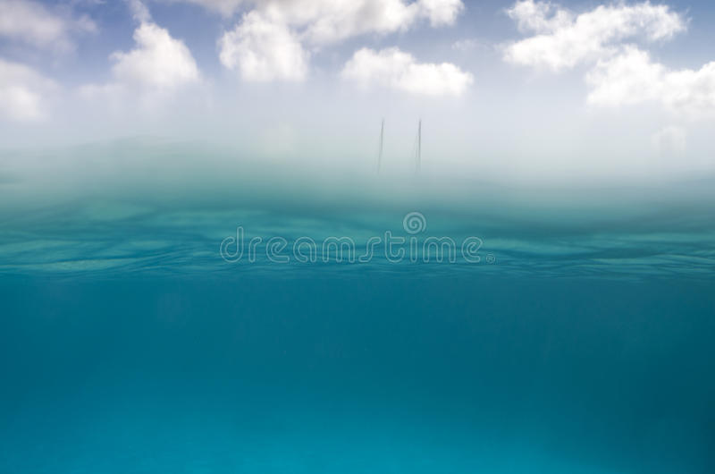 Underwater scene in the bottom and sky with clouds on the top wi. Th two sailing boat as background royalty free stock photos