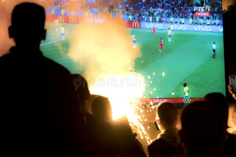 Undeutliche junge Fußballfane, die Fußballspiel auf der Straße aufpassen stockfotografie