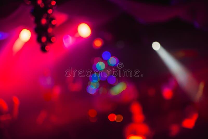 Undeutlicher abstrakter bunter farbiger Hintergrund im Nachtclub mit bokeh Rotlasern stockfotos