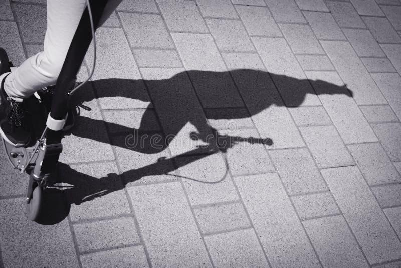 Undeutlicher Schatten des Elterngehens und ein Kind auf einem Sto?roller lizenzfreies stockbild