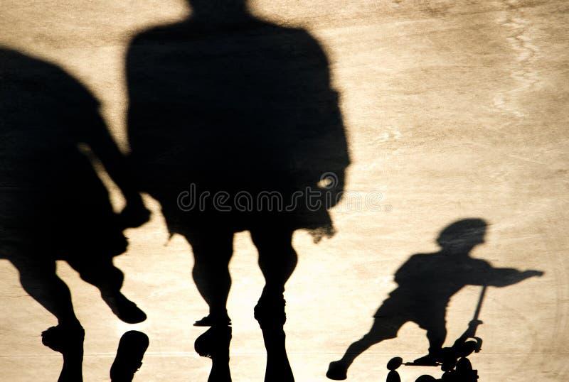 Undeutlicher Schatten von Eltern mit einem Kind auf einem Stoßroller lizenzfreies stockbild