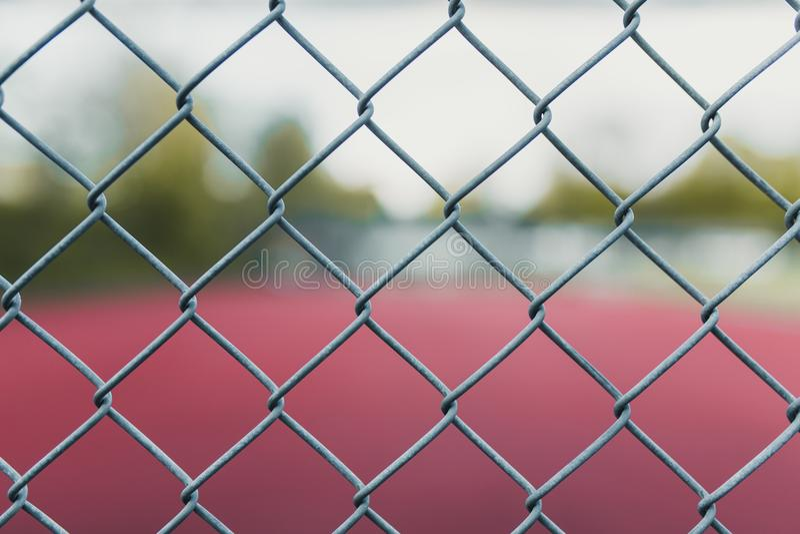 Undeutlicher Tennisplatz mit Fokus auf einem Zaun stockbilder
