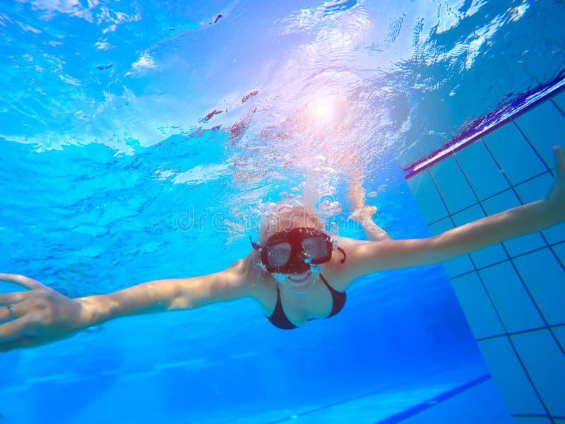 Undewater da natação da jovem mulher na piscina foto de stock