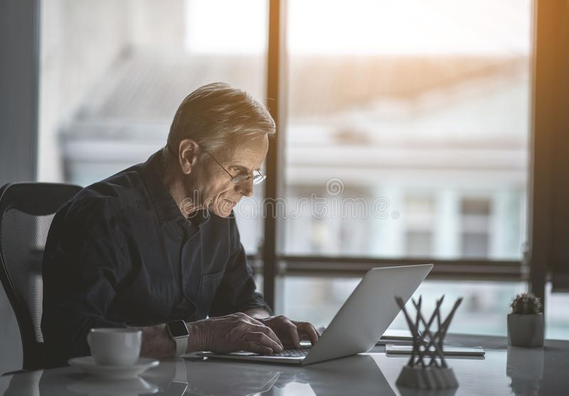 Undistracted älterer Mann, der im Laptop merkt stockbild