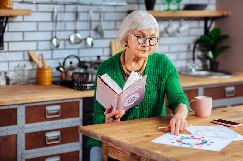Undistracted comely aged lady studying vedic charts and book. Studying vedic books. Undistracted comely aged lady wearing glasses and jade green apparel studying stock photos