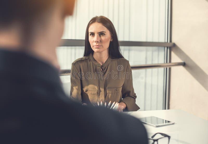 Undistracted Mädchen, das mit Partner an der Arbeit sagt stockbilder